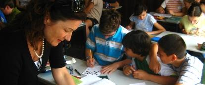 Students listen to a young Teaching volunteer in Romania while an older volunteer prepares for the lesson